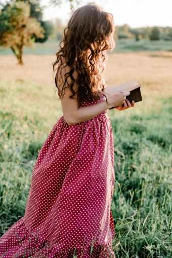 fille en robe a pois rouges et blancs holding book